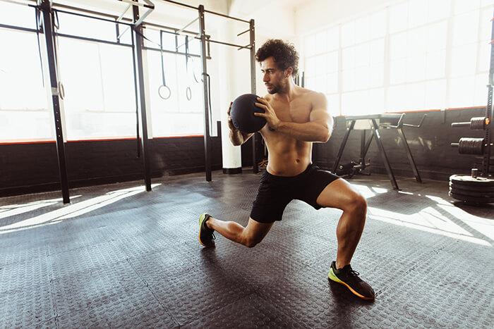 man training core muscles medicine ball