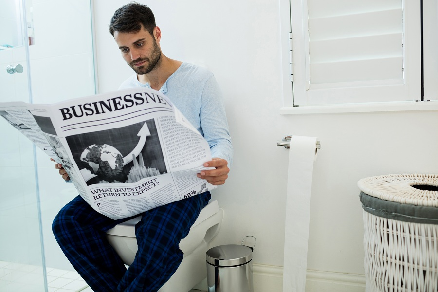 man sitting on toilet while reading a newspaper in the morning