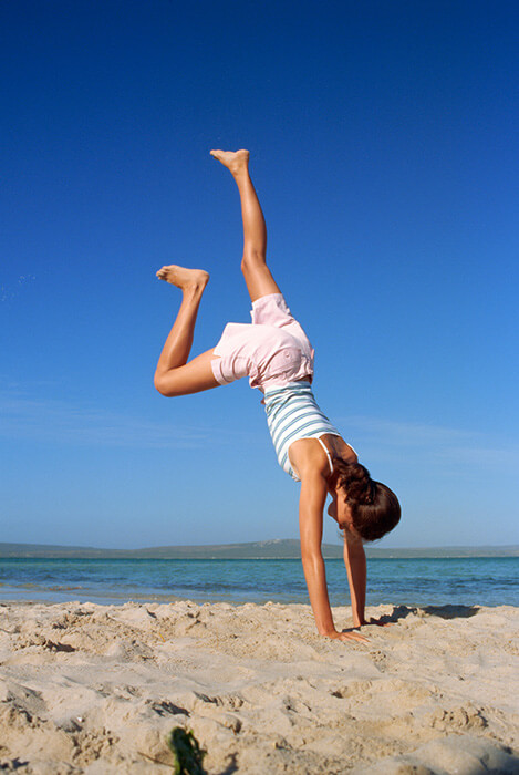 woman handstand exit on beach